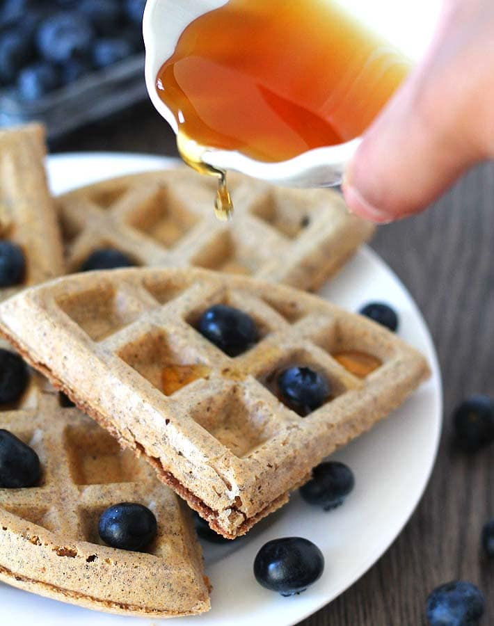 Maple syrup in a small white ceramic cup being poured onto a plate of Easy Vegan Gluten Free Waffles, waffles are garnished with fresh blueberries.