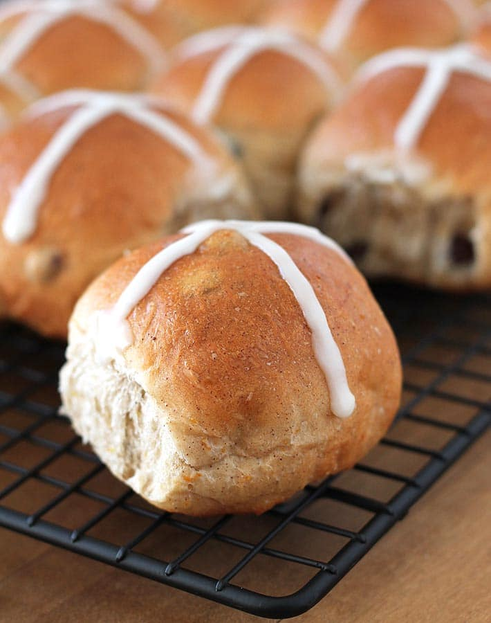 Vegan Hot Cross Buns just out of the oven on a black wire cooling rack.