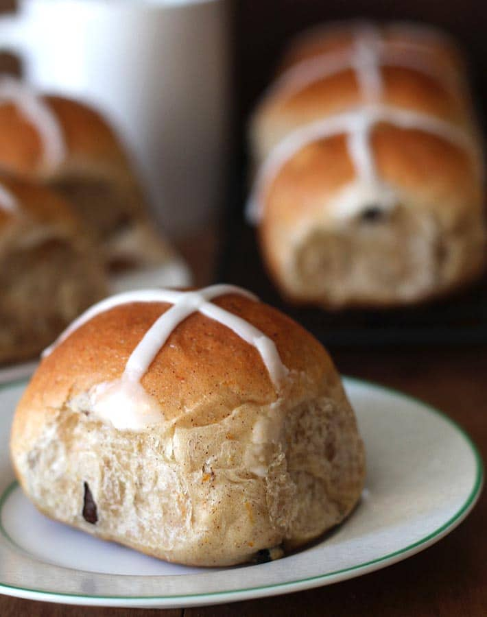 An up close shot of Vegan Hot Cross Buns, one is sitting on a plate while the others are sitting behind it.