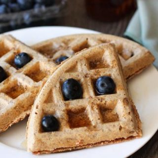 Easy Vegan Gluten Free Waffles on a white plate, a green cloth napkin sits to the right with a fork on top of it, waffles are garnished with fresh blueberries, and a container of blueberries sits behind the plate.