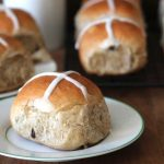 Vegan Hot Cross Buns sitting on a light brown wooden table, one bun sitting on a plate in the forefront.