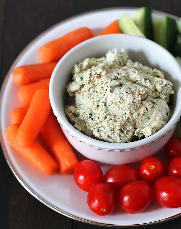 Garlic herb vegan almond cheese spread on a plate with veggies for dipping.