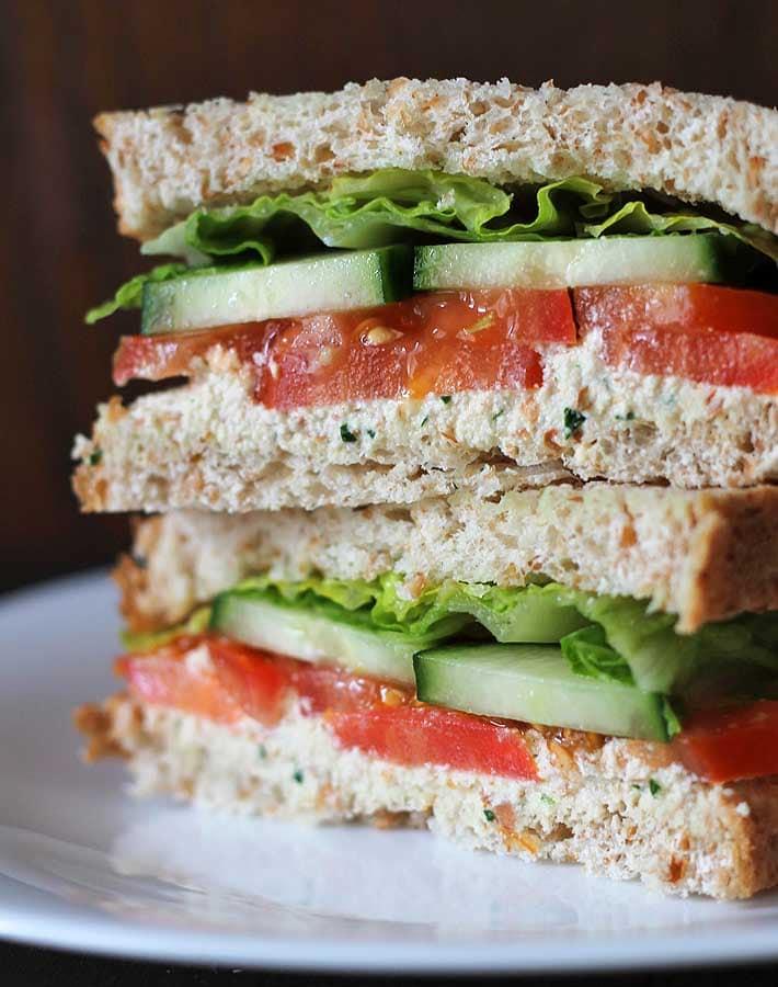 Garlic herb vegan almond cheese spread on a veggie sandwich.