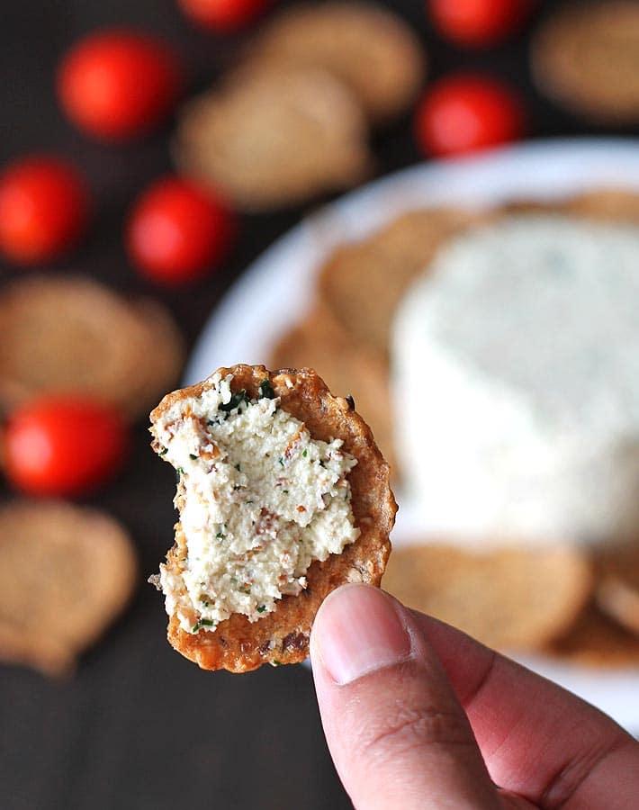 Close up shot of garlic herb vegan almond cheese spread.