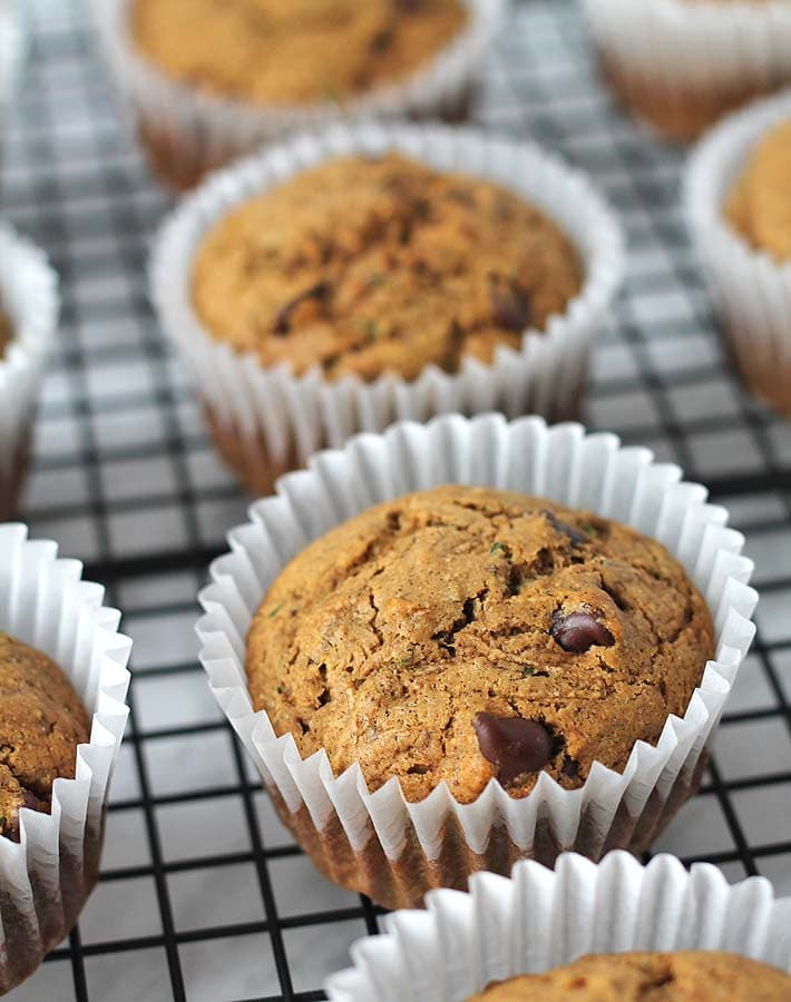 Vegan Gluten Free Zucchini Chocolate Chip Muffins sitting on a cooling rack.