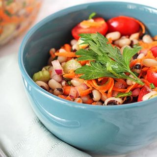 Simple Black-Eyed Pea Salad in a blue bowl with a spoon on the side.