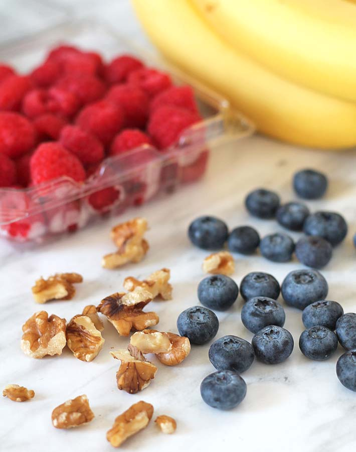 Bananas, raspberries, and blueberries all sitting on a marble surface, ingredients for a Berry Coconut Breakfast Bowl