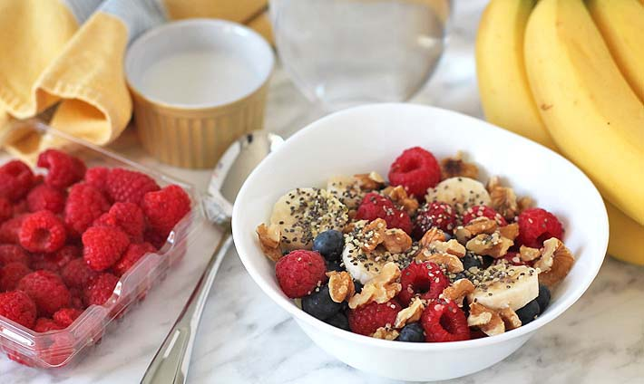 A Berry Coconut Breakfast Bowl on a marble surface surrounded by bananas, raspberries, a spoon, a glass of water, and a ramekin with coconut milk