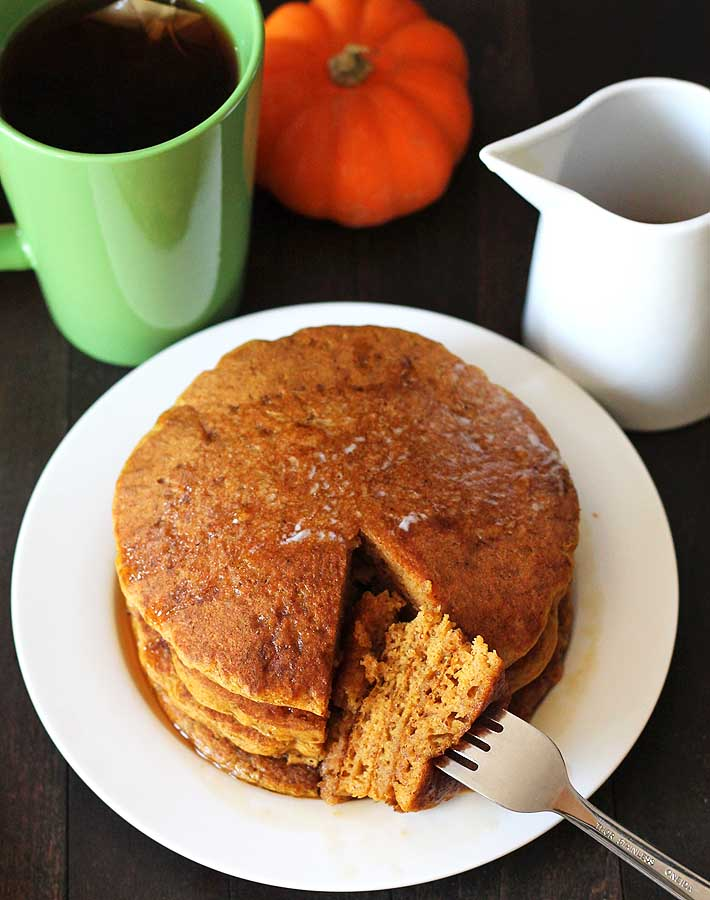 Vegan gluten free pumpkin pancakes sitting on a white plate with a cup of tea off to the left and a small cup of syrup on the right