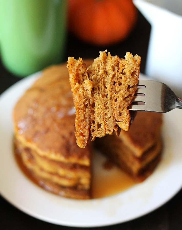 A close up shot of vegan gluten free pumpkin pancakes showing the fluffy insides