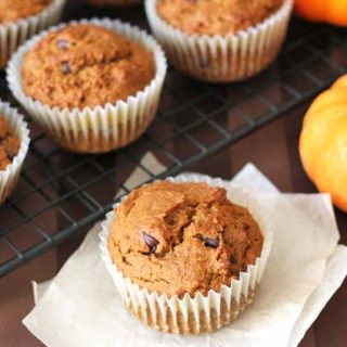 Vegan Gluten Free Pumpkin Spice Muffins sitting on a cooling rack with one muffin sitting on two pieces of parchment paper