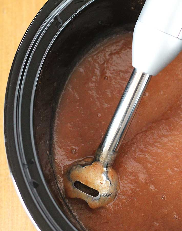 A stick blender sitting an a slow cooker after blending a batch of slow cooker applesauce