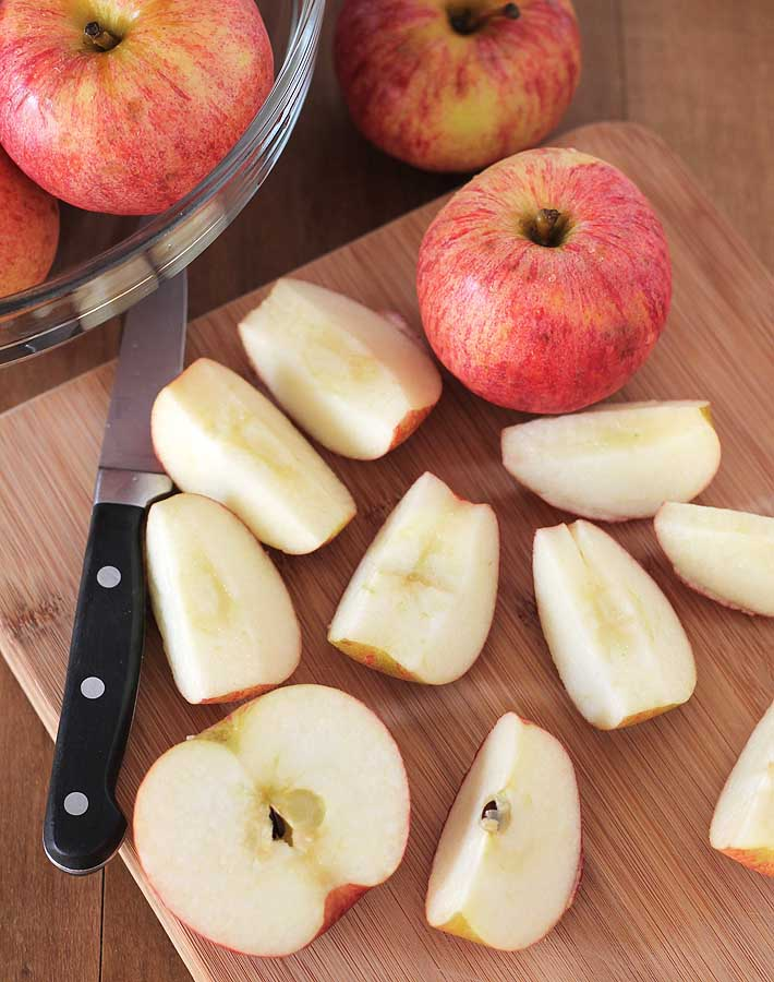 Cut apples on a cutting board being prepared to make slow cooker applesauce