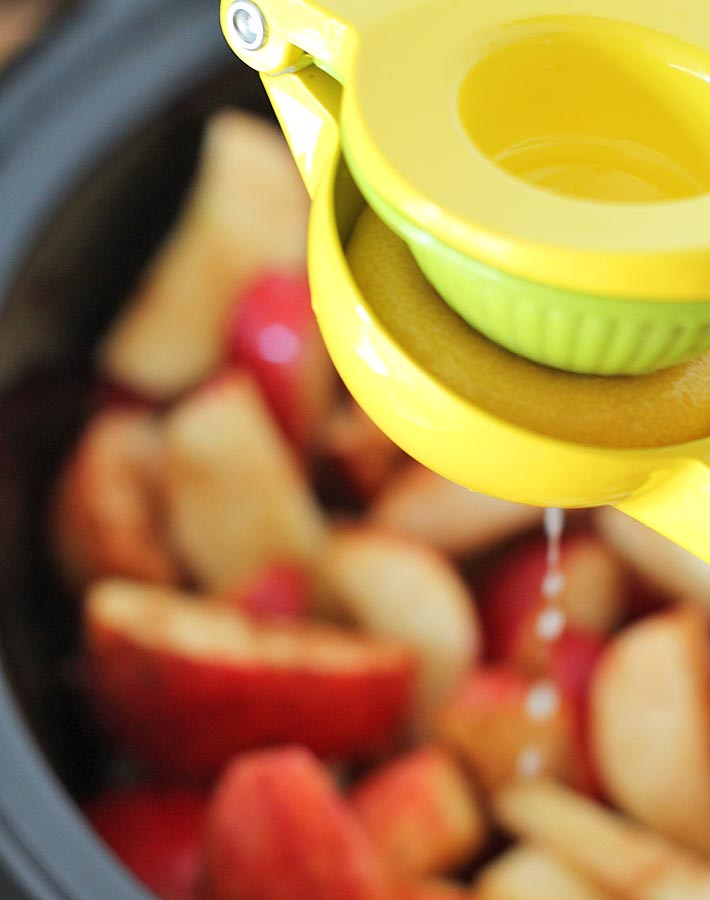 Cut apples in a slow cooker and a lemon squeezer above with lemon juice being squeezed onto the apples