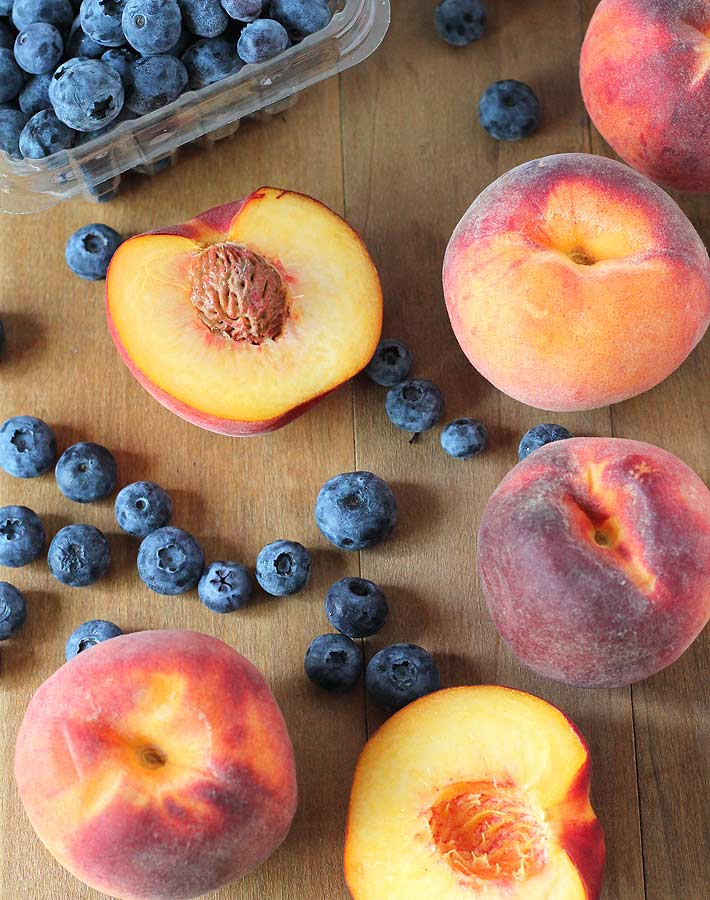 Peaches and blueberries on a wooden table, ingredients to make a Vegan Peach Blueberry Crisp
