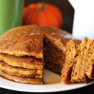 A stack of four vegan gluten free pumpkin pancakes with a wedge cut out of them
