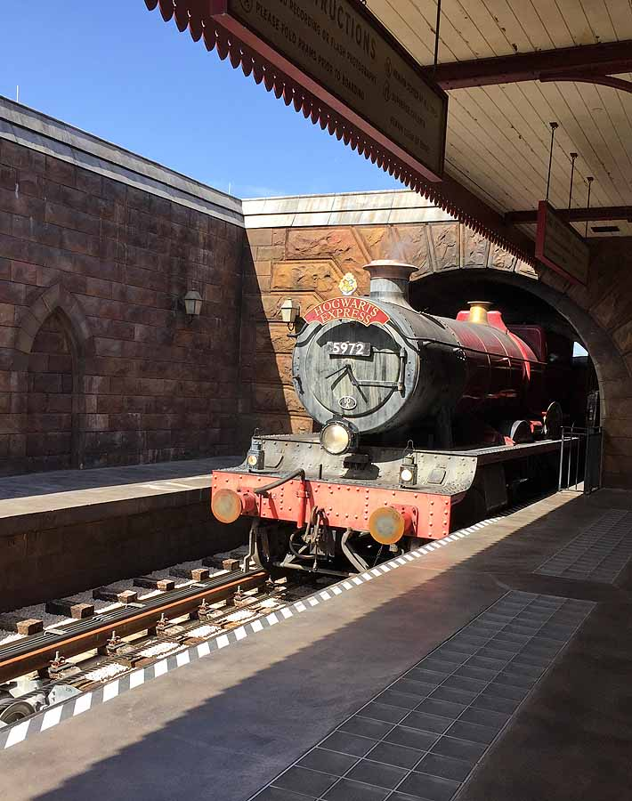 The Hogwarts Express train at Universal Studios Orlando coming out of a tunnel.