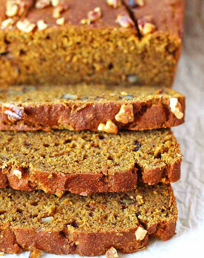 An up close shot of a loaf of Vegan Gluten Free Pumpkin Banana Bread with three slices in front of it.