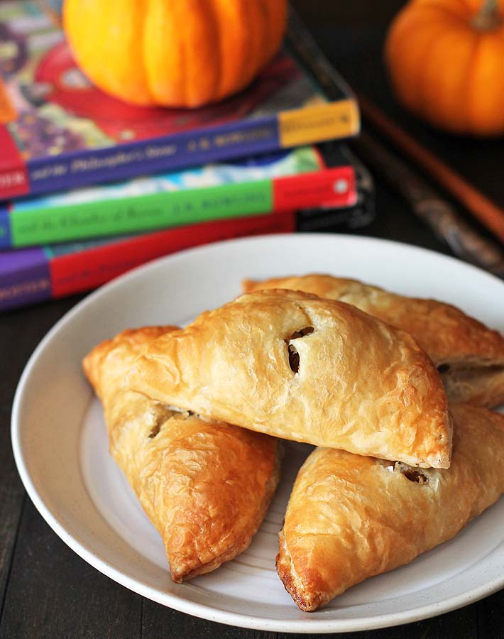 An up close shot of easy to make pasties sitting on a plate with mini pumpkins and three Harry Potter books sitting behind the plate.