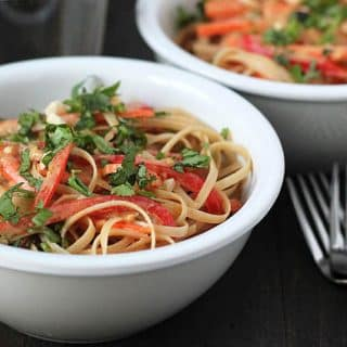 A bowl of vegan peanut noodles garnished with chopped cilantro and chopped peanuts with two forks sitting to the left of the bowl.
