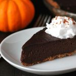 A slice of vegan chocolate pumpkin pie on a small white plate with a spoonful of coconut whipped cream on top.