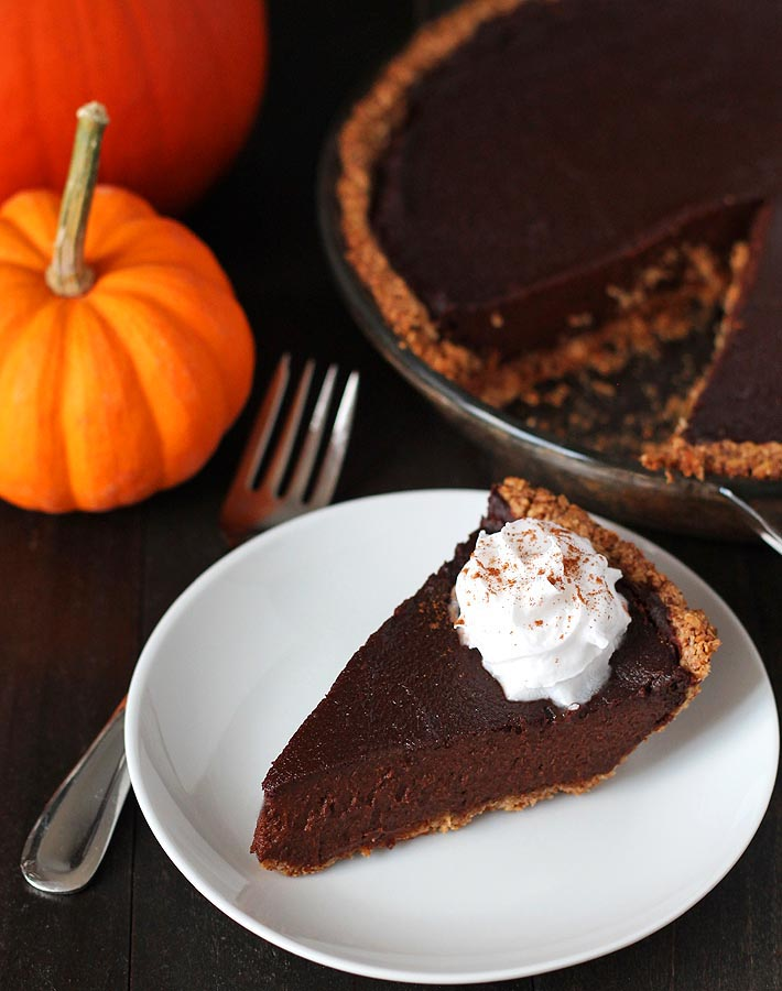 A slice of vegan chocolate pumpkin pie sitting on a small white plate with coconut whipped cream garnish, with a fork to the left and the rest of the pie to the right.
