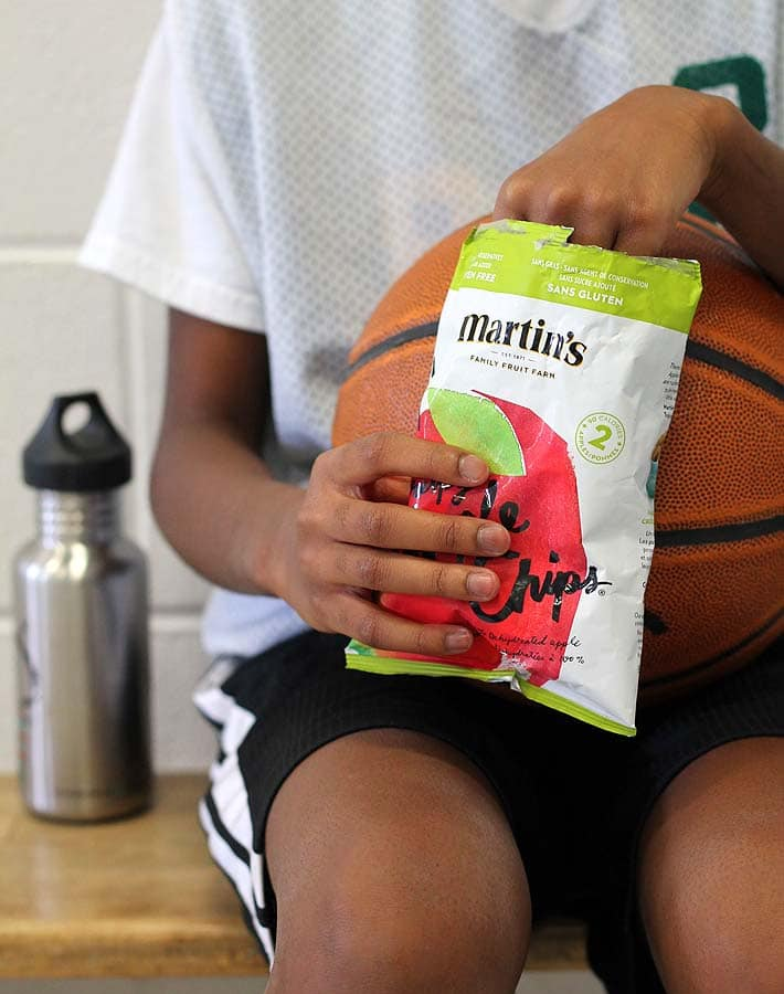 Vegan Snack Ideas for Active Kids plus an Easy Yogurt Dip Recipe: Child sitting on basketball game sidelines eating apple chips from a bag.