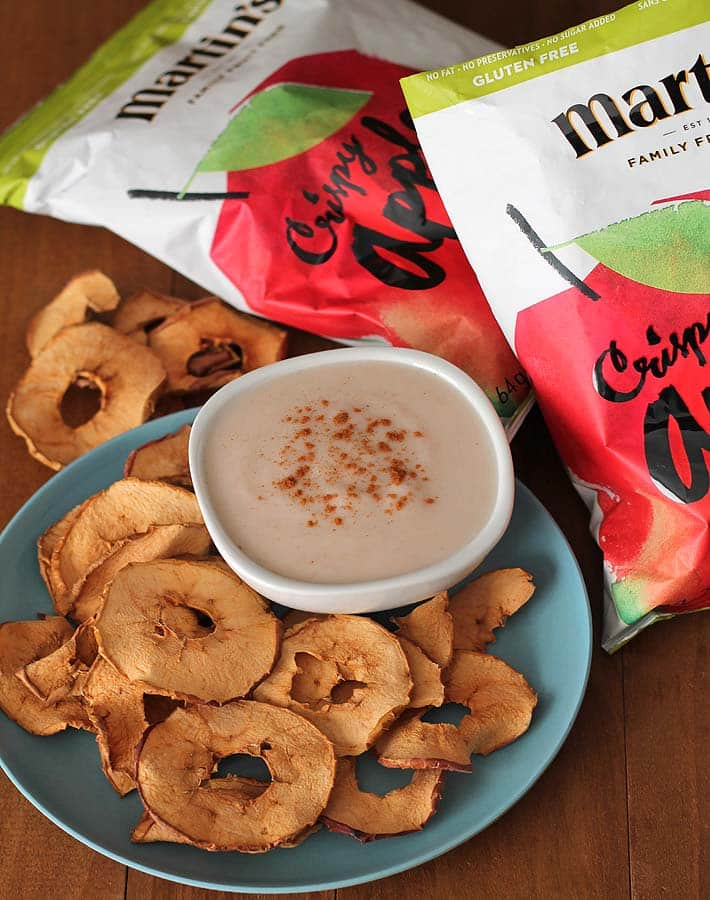 Vegan Snack Ideas for Active Kids plus an Easy Yogurt Dip Recipe: Overhead shot of a plate of apple chips alongside a bowl of dip with two bags of apple chips sitting above the plate.