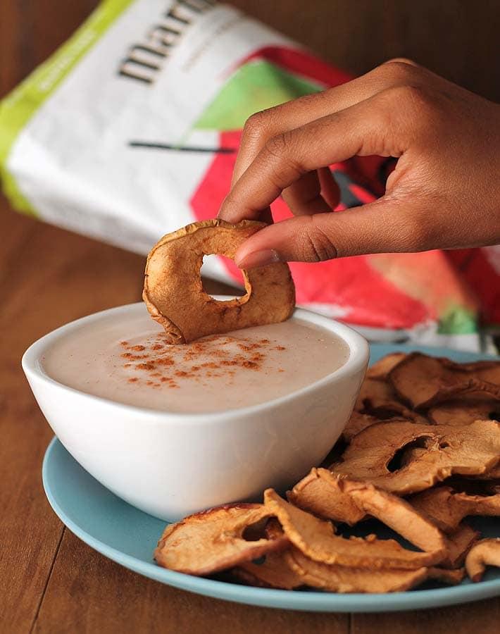 Vegan Snack Ideas for Active Kids plus an Easy Yogurt Dip Recipe: An apple chip being dipped into a yogurt dip.