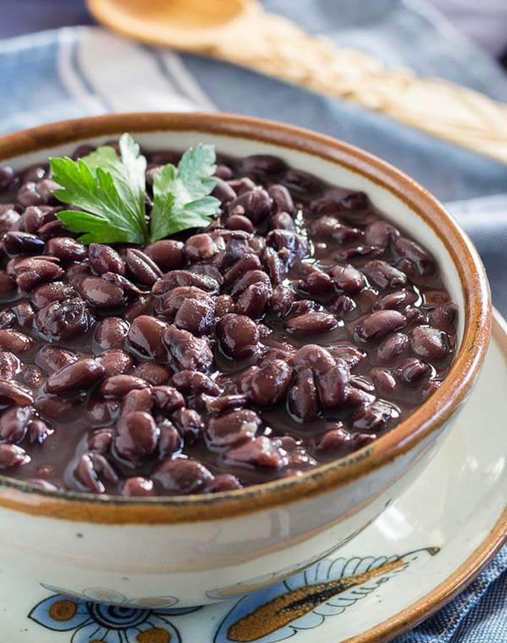 Easy Instant Post Vegan Recipes - Cooked black beans in a bowl with a sprig of cilantro on top of the beans.