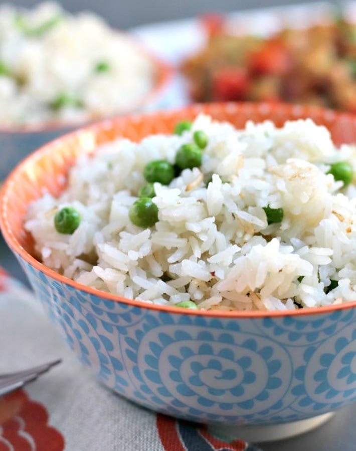 Easy Instant Pot Vegan Recipes - Instant Pot Coconut Jasmine Rice with green peas in a blue and white bowl.