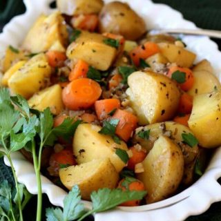 Easy Instant Pot Vegan Recipes - Instant Pot Potato Carrot Medley in a white serving dish with a small bunch of fresh parsley sitting on the side of the dish.