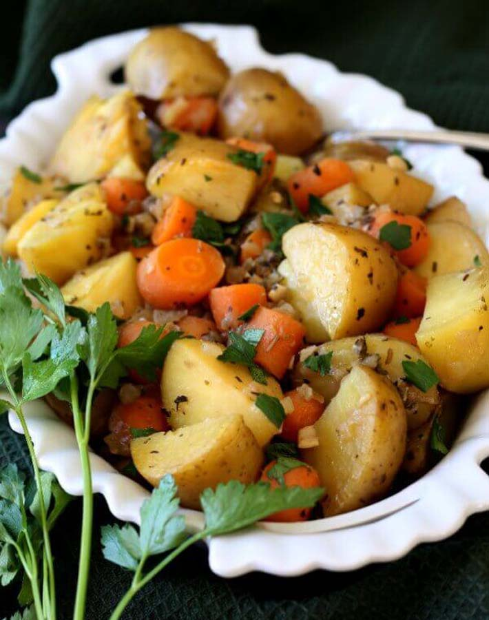 Easy Instant Post Vegan Recipes - Instant Pot Potato Carrot Medley in a white serving dish with a small bunch of fresh parsley sitting on the side of the dish.