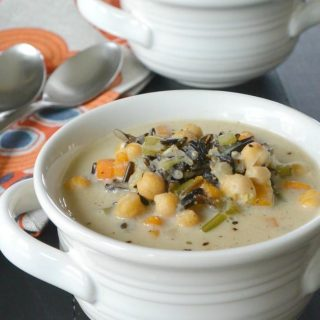 Easy Instant Pot Vegan Recipes - Instant Pot Vegan Wild Rice Soup in a white bowl with two spoons sitting to the left and another bowl of soup sitting behind it.