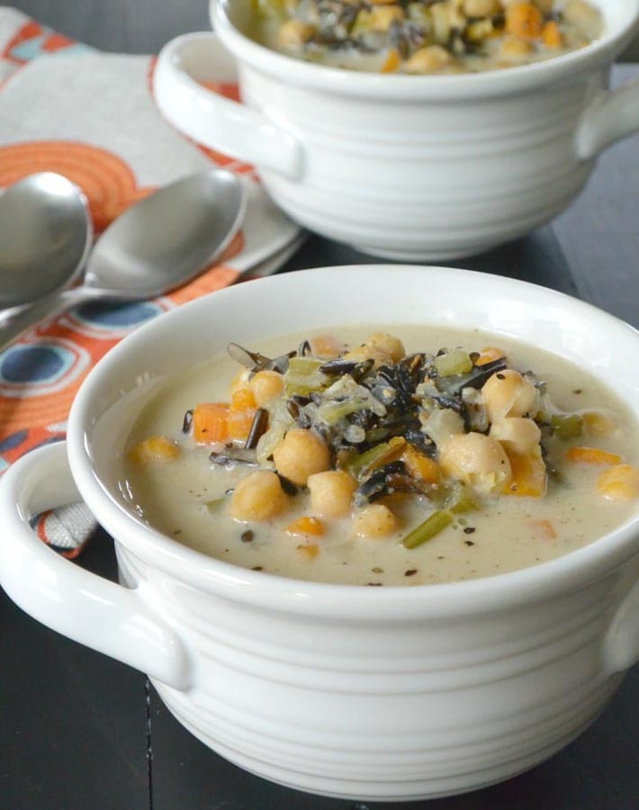 Easy Instant Post Vegan Recipes - Vegan Wild Rice Soup in a white bowl with two spoons sitting to the left and another bowl of soup sitting behind it.