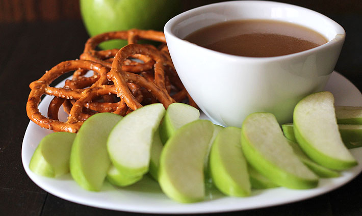 A small white bowl filled with vegan maple caramel sauce sitting on a white plate with sliced green apples and pretzels for dipping.