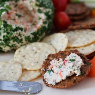 A cracker with some Vegan Vegetable Almond Cheese Ball spread on it, cracker is sitting on a board with the cheese ball behind it and cut up vegetables surround the cheese ball.