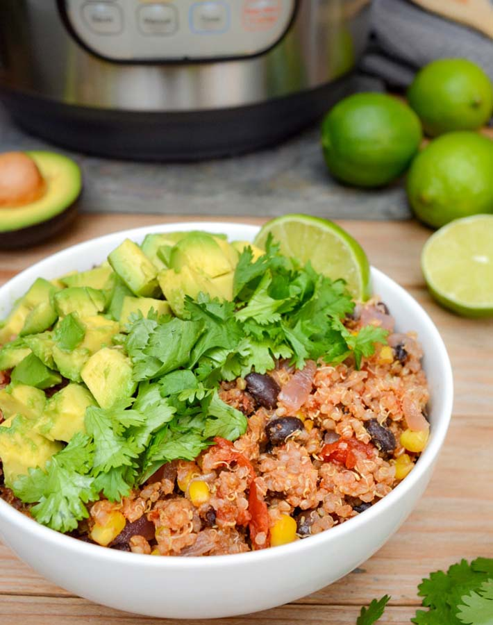 Easy Instant Pot Vegan Recipes - Instant Pot Mexican Quinoa Bowl on a wooden table with the Instant pot Pressure cooker in the background and cut limes in the background.