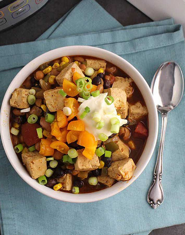 Easy Instant Pot Vegan Recipes - Overhead shot of Instant Pot vegan chili in a bowl on a blue tablecloth with a spoon to the right of the bowl.