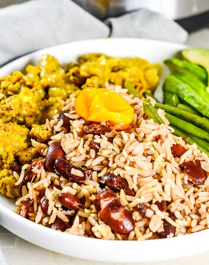 Easy Instant Pot Vegan Recipes - Instant Pot Jamaican Rice and Peas in a white bowl with green beans to the right and curried vegetables to the left.