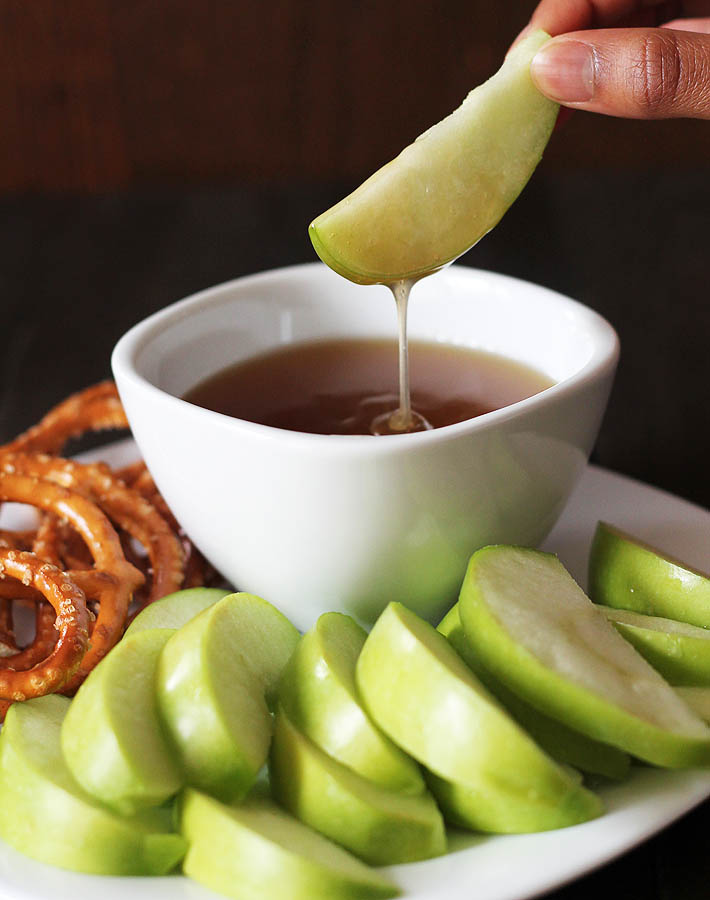 A slice of green apple just dipped in a bowl of vegan maple caramel sauce with more sliced green apples and pretzels sitting on a plate for dipping as well.