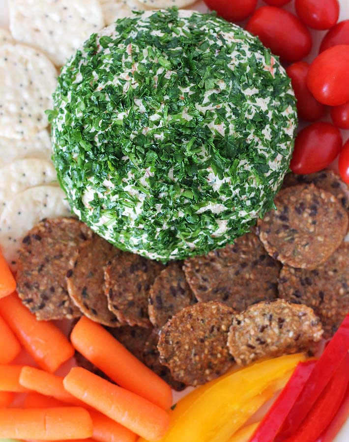 A Vegan Vegetable Almond Cheese Ball rolled in finely chopped parsley sitting on a wooden board surrounded by two types of crackers and baby carrots, cherry tomatoes, and sliced red and yellow peppers.