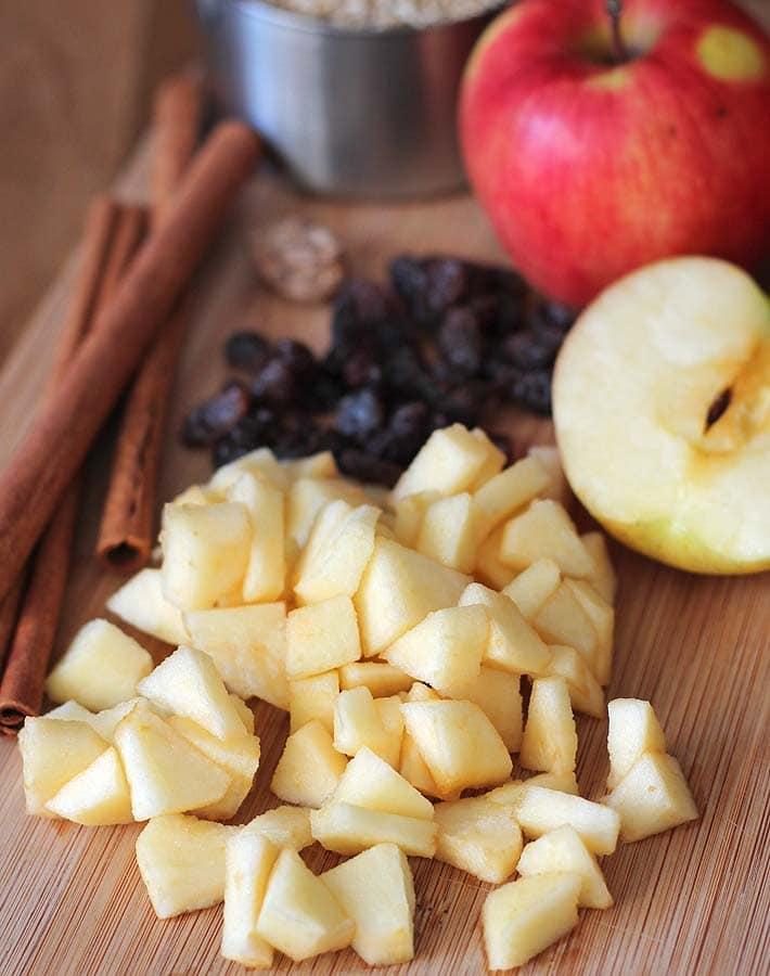 Ingredients for Apple Spice Instant Pot Steel Cut Oats sitting on a bamboo cutting board (fresh apples, raisins, cinnamon, nutmeg, and steel cut oats).