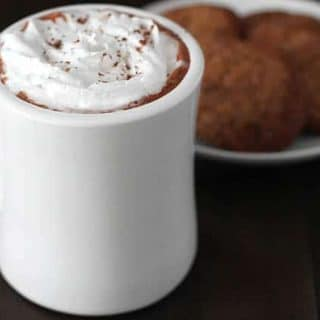 Creamy Vegan Hot Chocolate topped with coconut whipped cream in a white mug with a plate of cookies on a plate behind it.