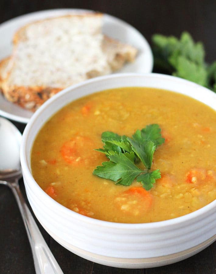 Easy Instant Post Vegan Recipes - Curried Instant Pot Split Pea Soup in a white bowl garnished with fresh parsley, a spoon sits to the left of the bowl and a white plate with a slice of buttered bread is in the background.