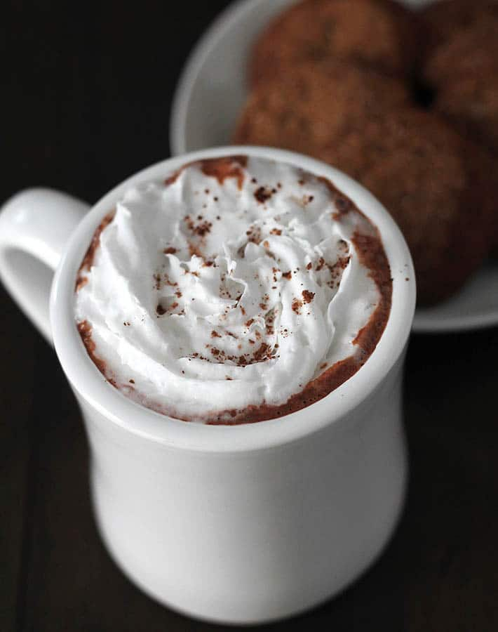 Coconut whipped cream topped Creamy Vegan Hot Chocolate in a mug on a dark wood table, a plate of cookies on a white plate behind the mug.