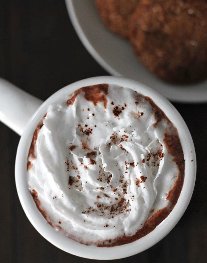 Overhead shot of a mug of Creamy Vegan Hot Chocolate, hot chocolate is topped with coconut whipped cream, mug is sitting on a dark wood table, a plate of cookies sit in the top right of the image.