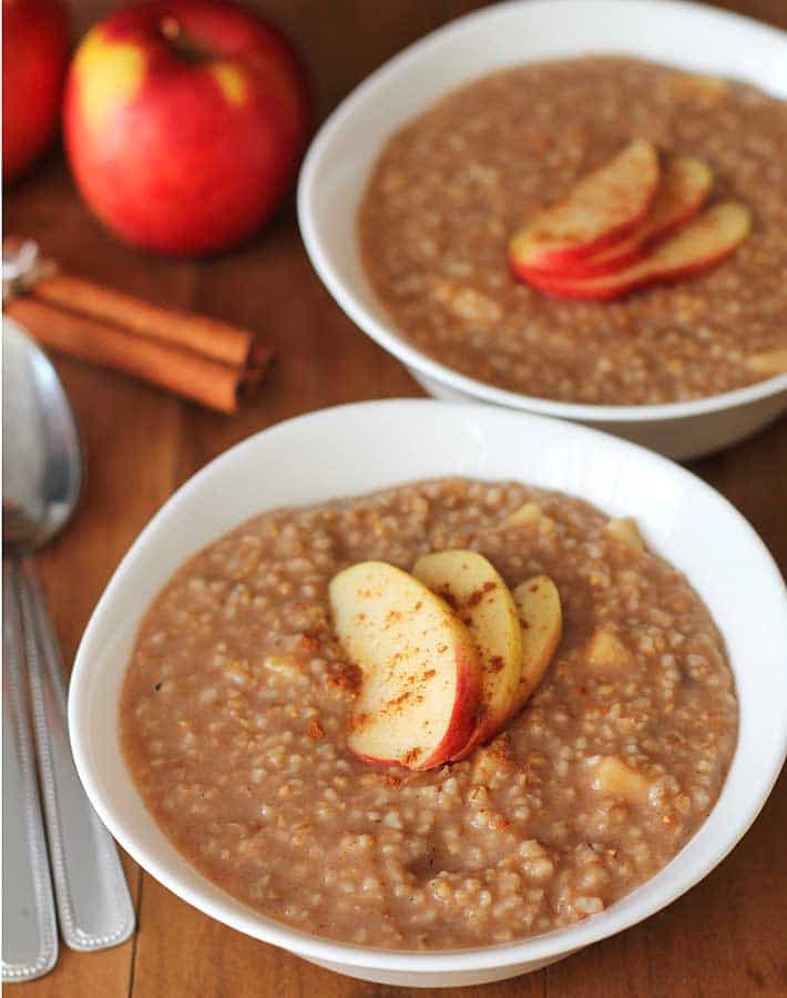 Apple Spice Instant Pot Steel Cut Oats in two white bowls with 3 fresh apple slices on top of each bowl of oat, bowls are sitting on a brown wood table.