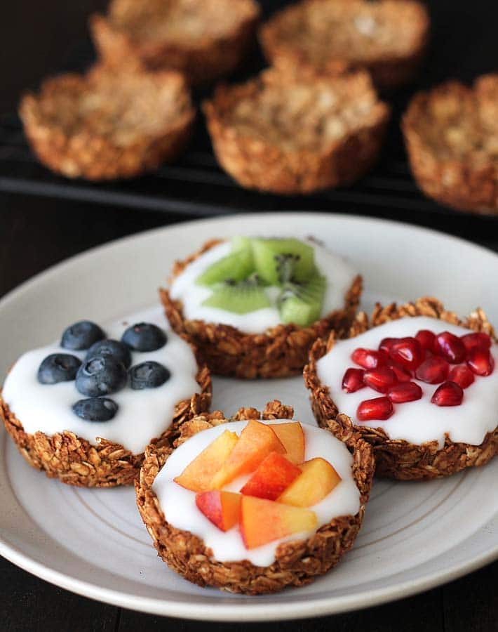 Four granola cups sitting on a plate, each are filled with vegan coconut yogurt, one is topped with fresh blueberries, another with fresh kiwi pieces, another with pomegranate arils, and the last with fresh nectarine pieces.