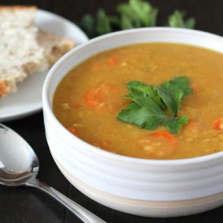A bowl of Curried Instant Pot Split Pea Soup in a white bowl, soup is garnished with a small bunch of fresh parsley, bowl is sitting on a black wood table, a small white plate with a slice of buttered bread sits in the background.